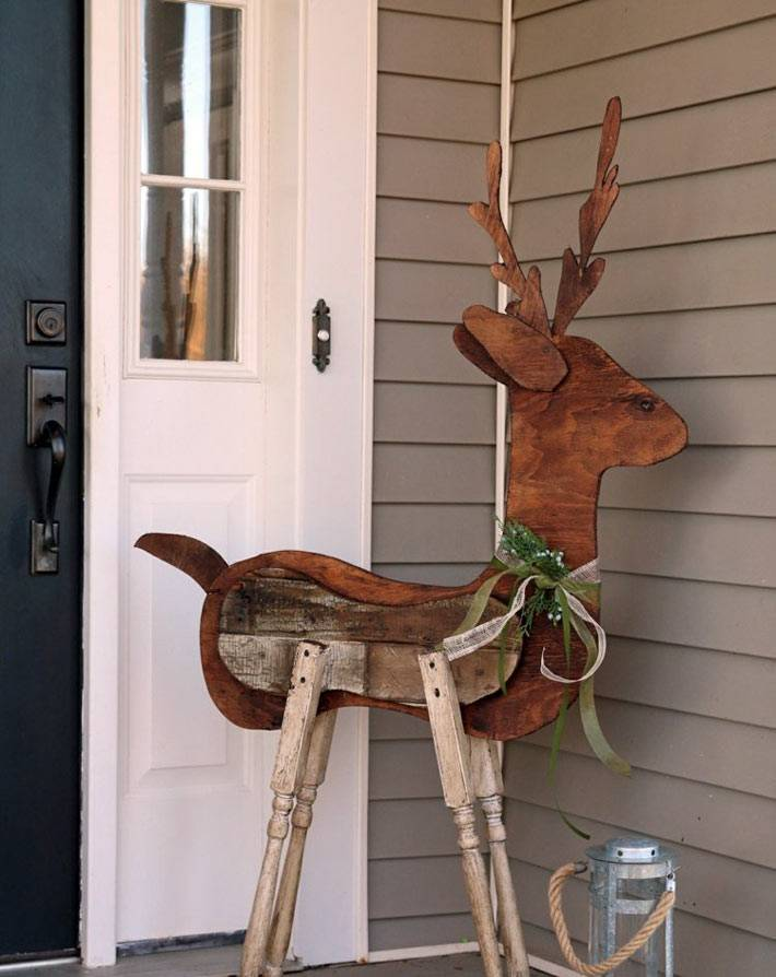 деревянный олень как новогоднее украшение при входе в дом