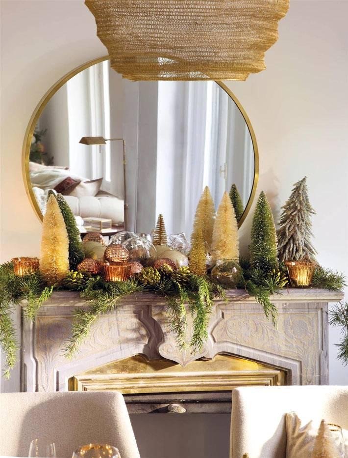 золотые подсвечники и маленькие елки на каминной полке фото