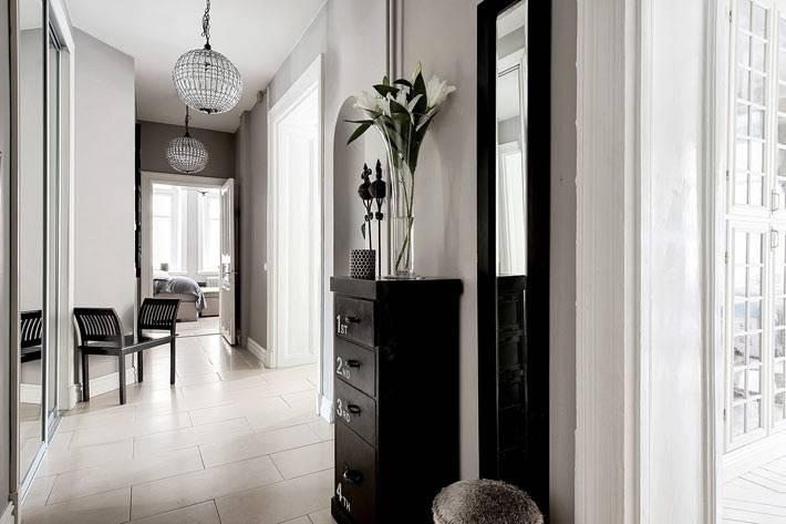 белые стены и люстра-шар в коридоре шведской квартиры