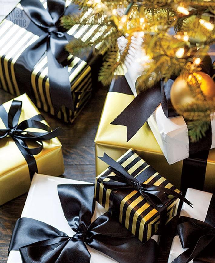 новогодние подарки в золотой бумаге с черными лентами