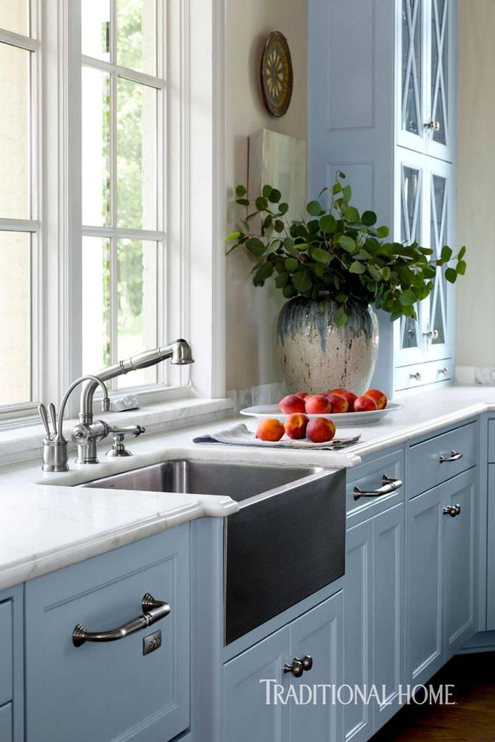 кухонная мойка из стали перед окном фото