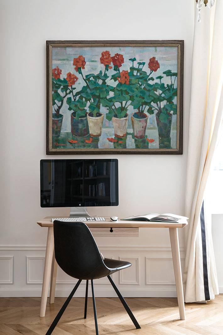 рабочий деревянный стол с черным стулом возле большой картины