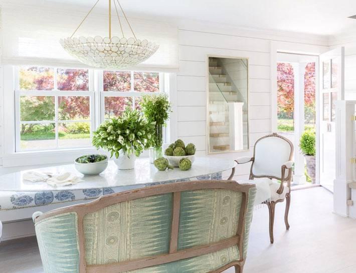 белый интерьер столовой комнаты с окнами на цветущий сад
