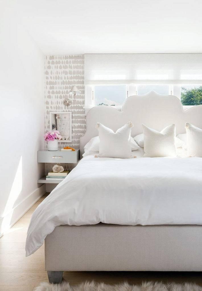 большаяя белая кровать с фигурным изголовьем в спальне