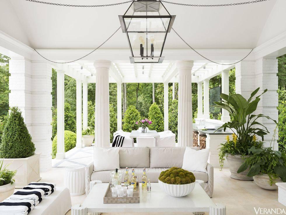 большая открытая белая терраса с обеденным столом и диванами фото