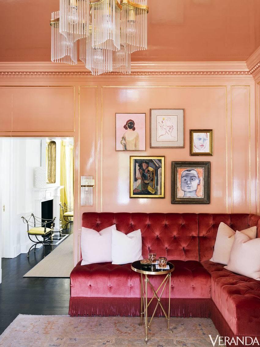 красный бархатный диван интерьере с персиковыми стенами