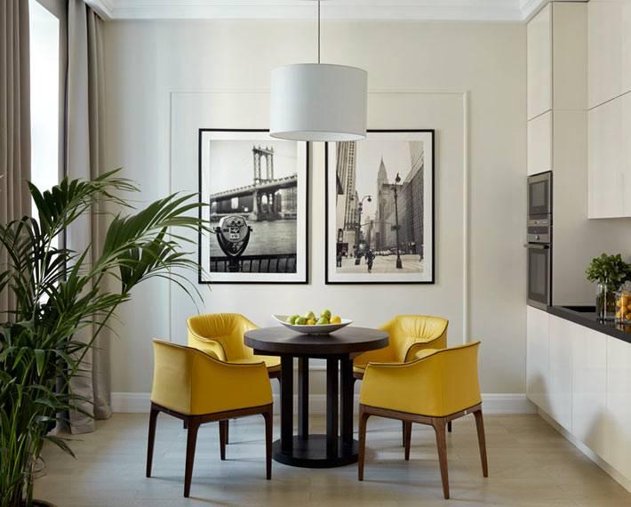 ярко-желтые стулья за обеденным круглым столом на кухне фото
