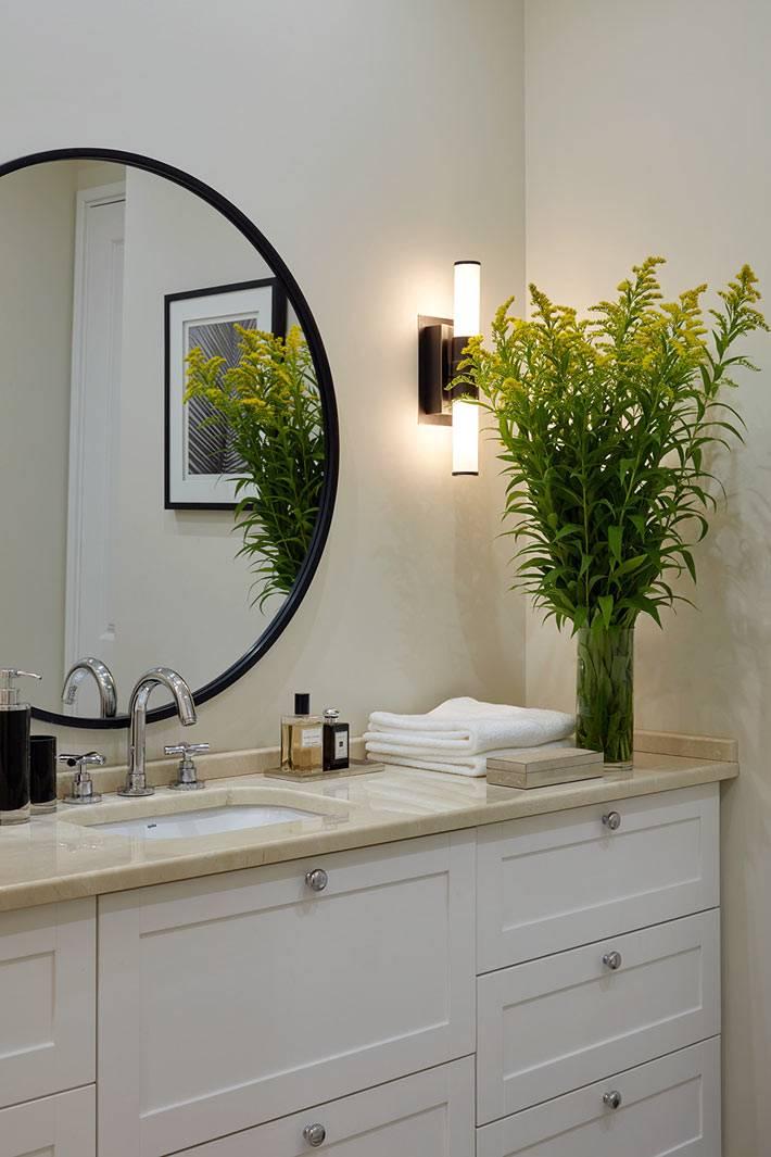 мраморная столешница и большое круглое зеркало в интерьере ванной комнаты