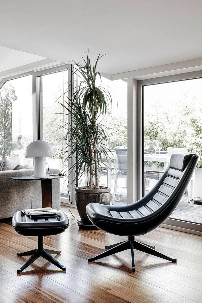 комфортное черное кресло с подставкой для ног