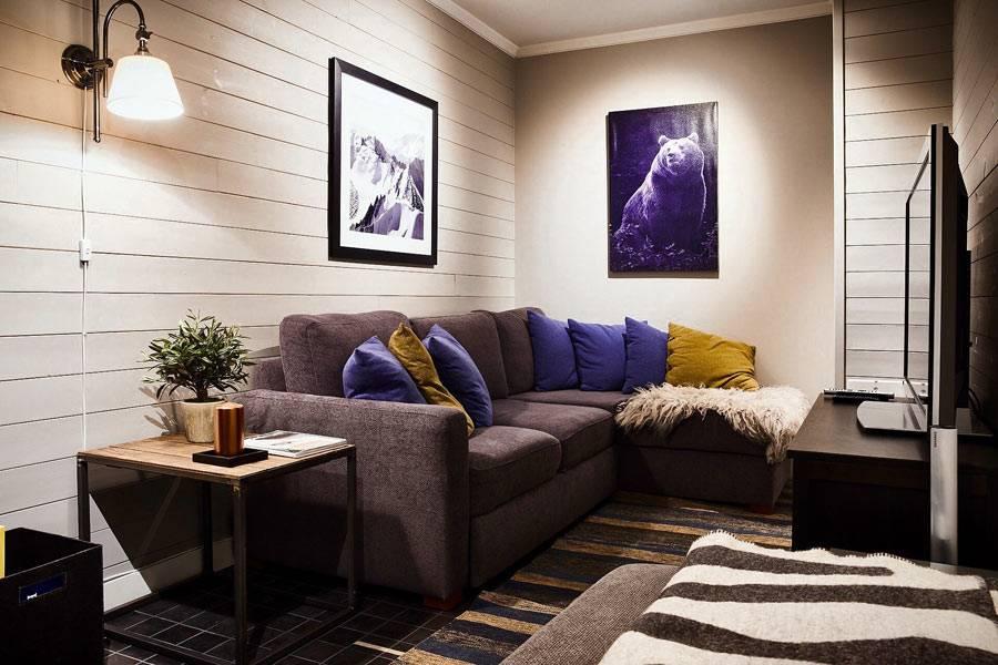 маленькая комната с угловым диваном и большим телевизором