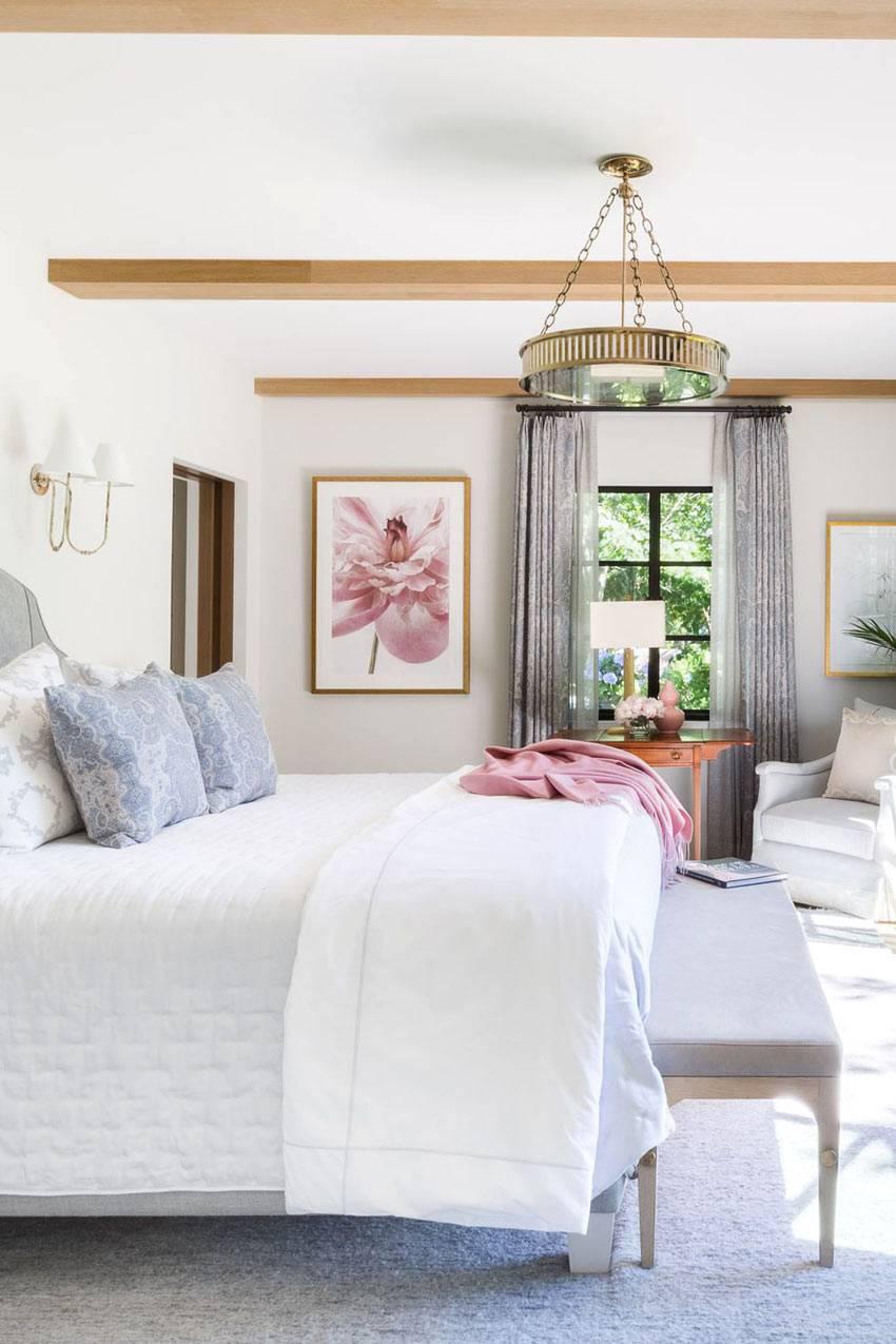 большая спальня с потолочными балками в светлых тонах