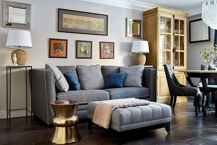 серый диван и пуф для оформления гостиной комнаты