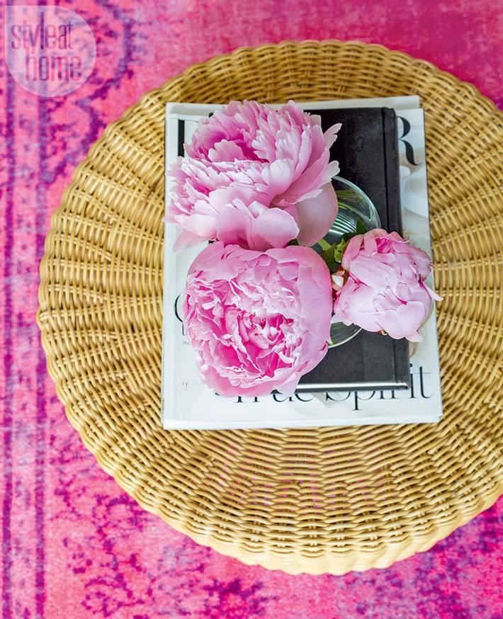 розовые пионы на плетеном столике в доме
