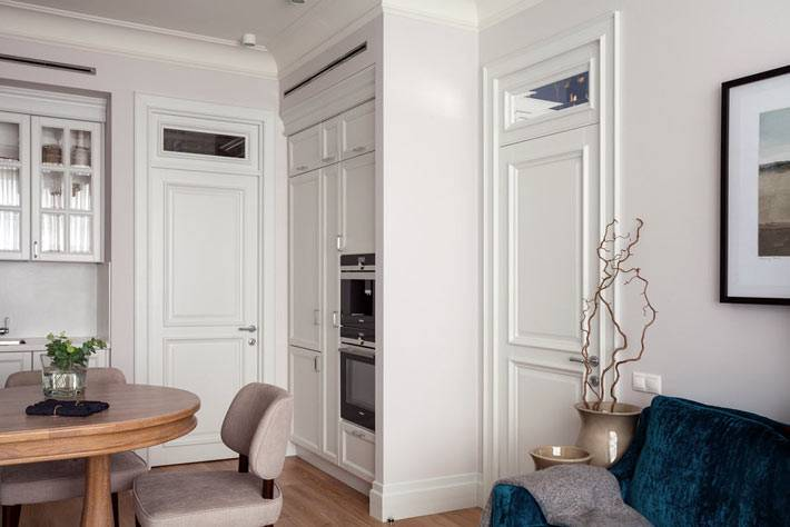 кухонные шкафы и встроенная техника в нишах комнаты
