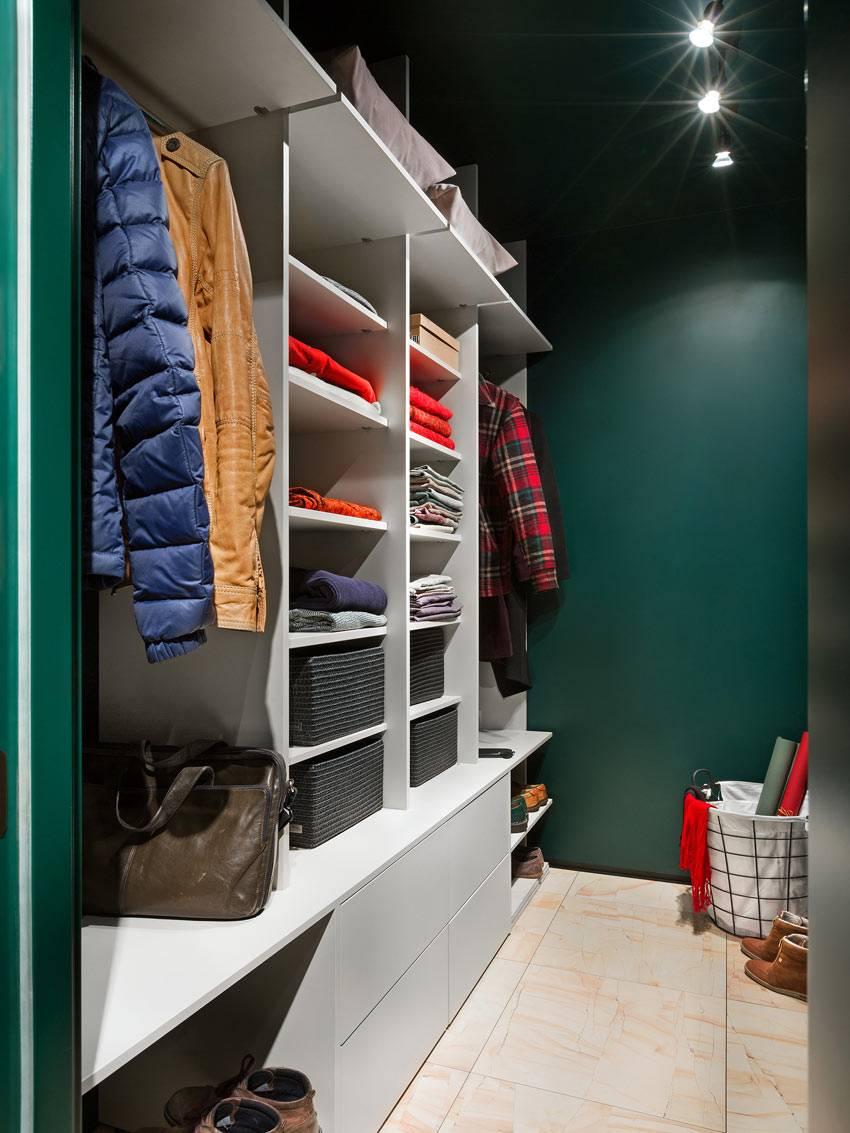гардеробная комната с зелеными стенами и белыми шкафами