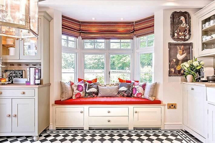 ярко-красный матрас с подушками на подоконнике в эркере