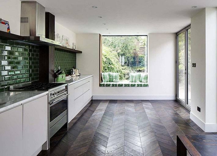 большое окно на кухне с матрасом и зелеными подушками