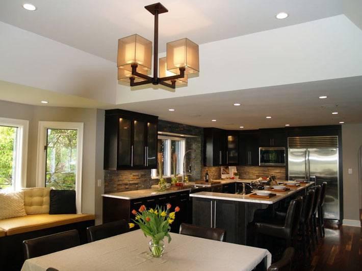 черная мебель на кухне с ярким желтым подоконником-сиденьем
