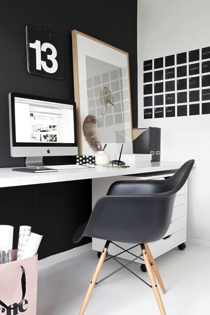 белый рабочий стол возле черной стены в интерьере