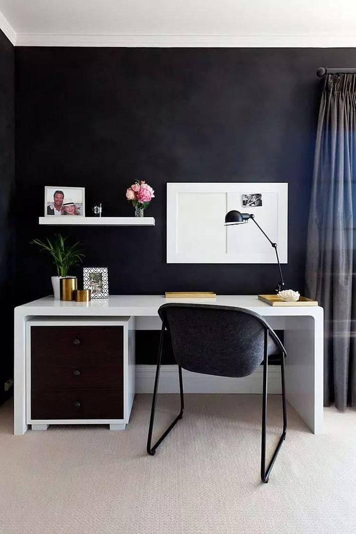 белый рабочий стол на контрасте с черной стеной в комнате