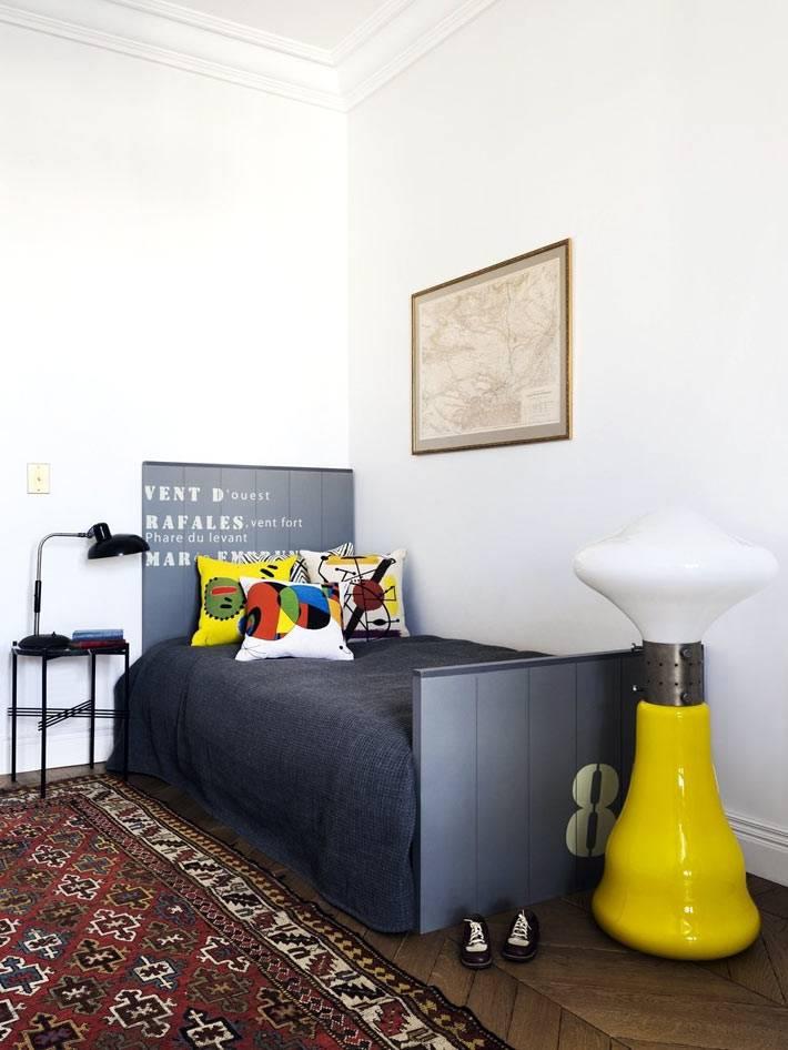 детская кровать серого цвета и желтый светильник на полу