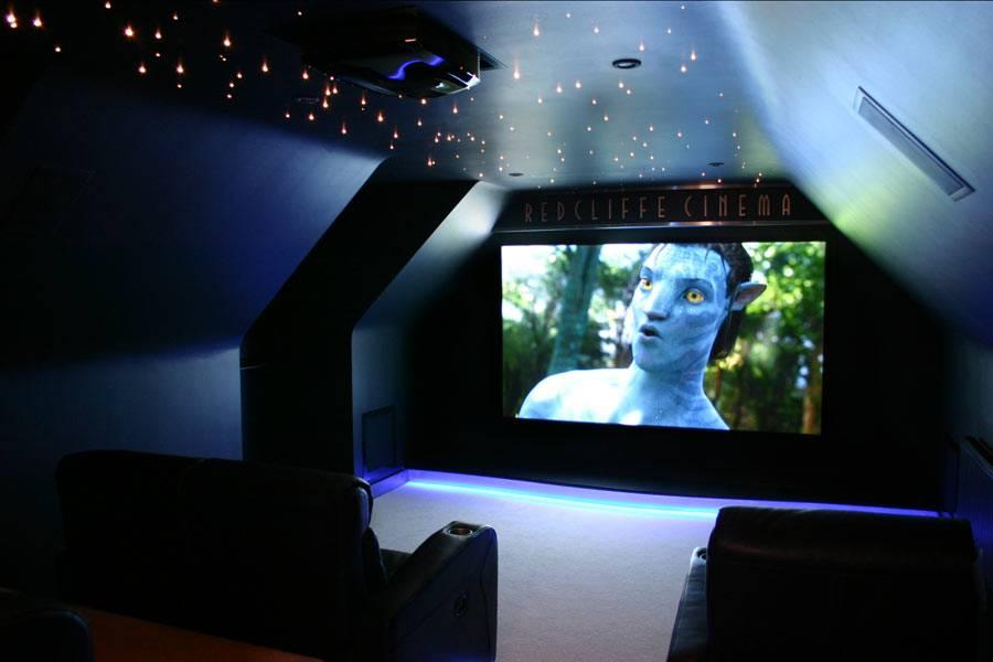 темная мансардная комната-кинотеатр с большим экраном