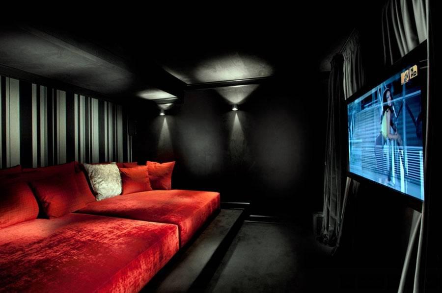 черная комната с красным бархатным диваном и большим тв