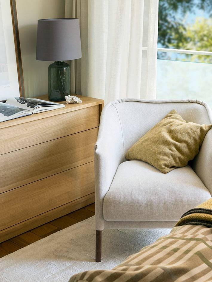 деревянный комод без ручек и кресло в спальне