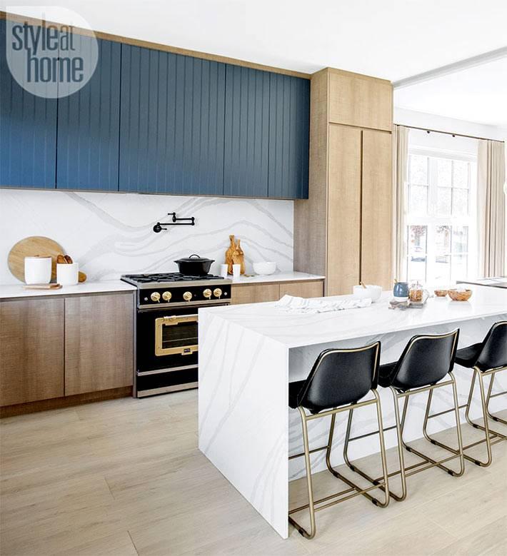 кухонный остров из мрамора с черными барными стульями