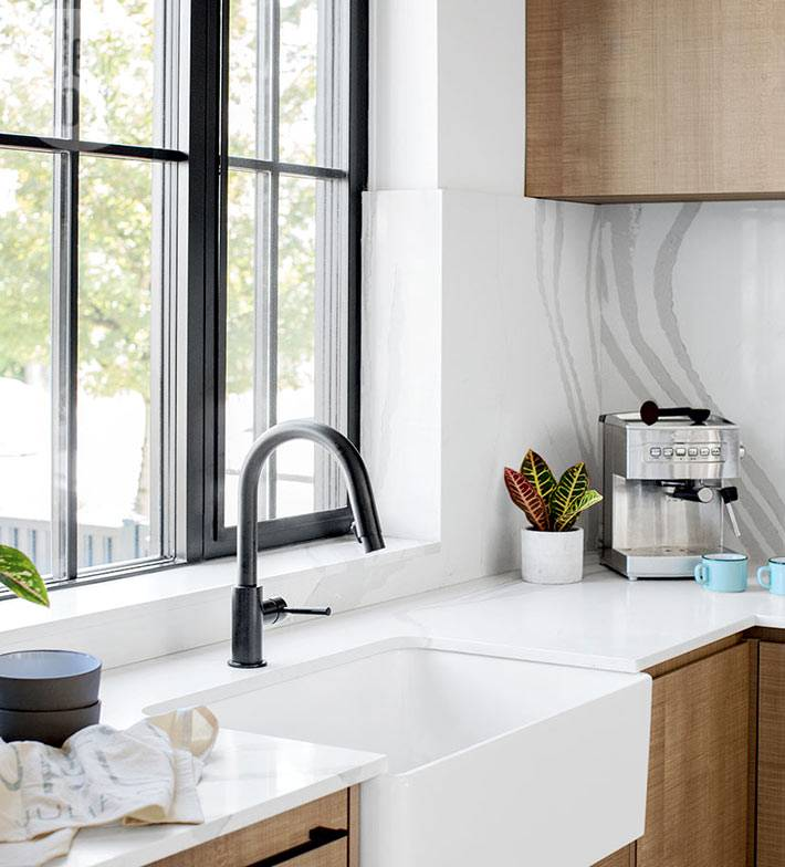 кухонная белая раковина находится возле окна