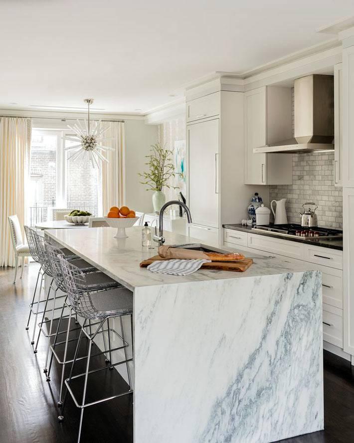 мраморный остров на большой белой кухне фото