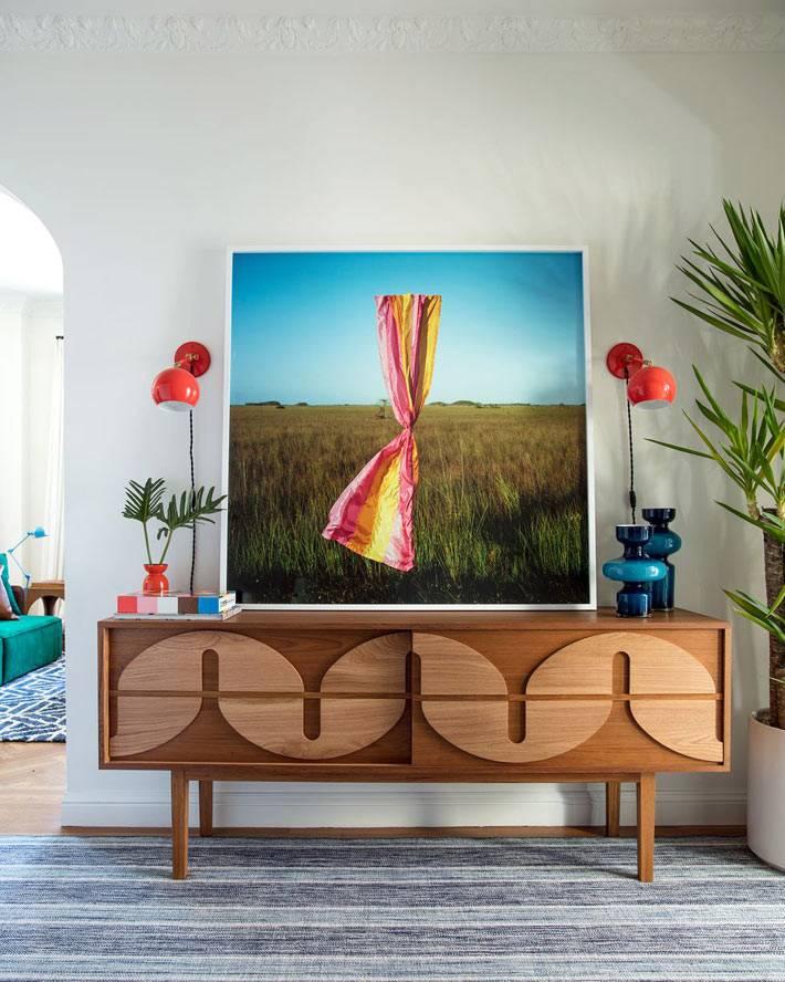 яркая картина и оранжево-красные бра на стене в холле