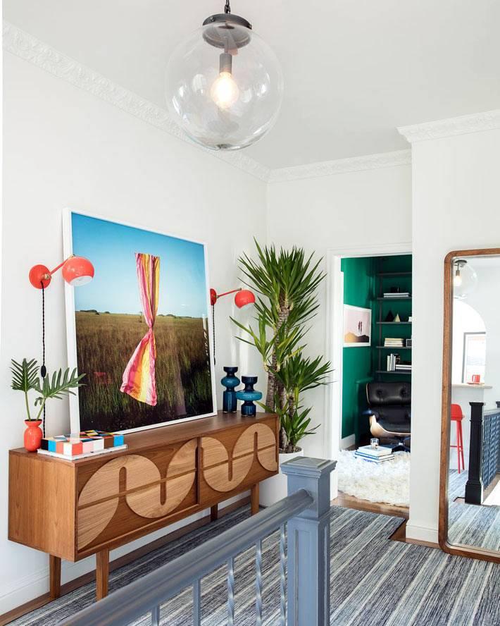 большое напольное зеркало и зеленое комнатное растение в грошке