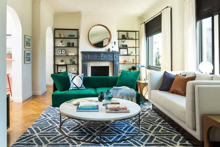 круглый мраморный стол и зеленый диван в интерьере гостиной