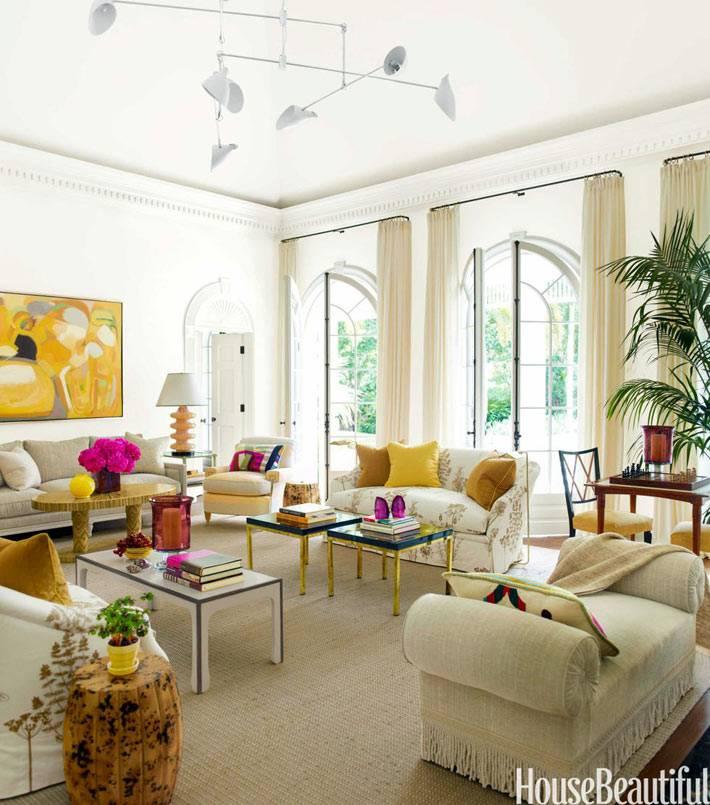 солнечный интерьер гостиной с большими арочными окнами