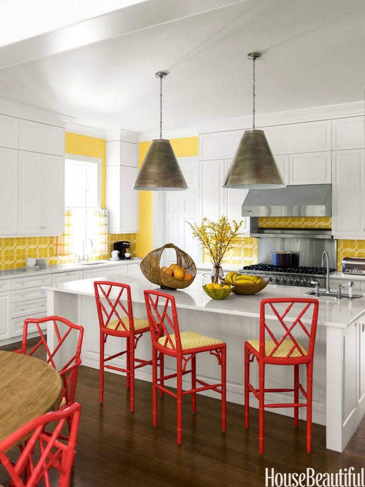 желтые стены на кухне с белой мебелью и красными стульями