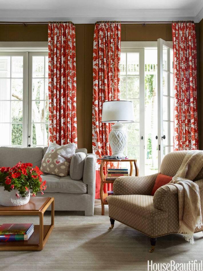 красные коралловые шторы в гостиной с коричневыми обоями