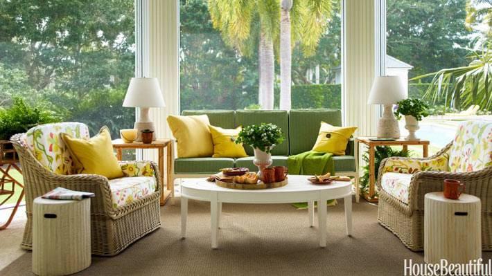 застекленная веранда с зеленым диваном и плетеной мебелью