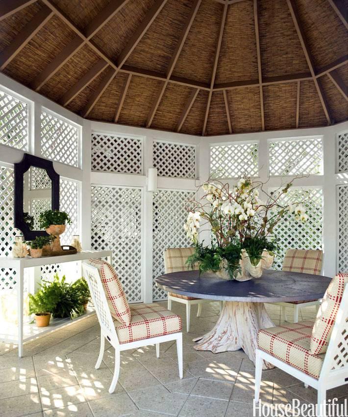 белая беседка с бамбуковой крышей и круглым столом