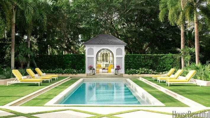 открытый бассейн во дворе с желтыми шезлонгами