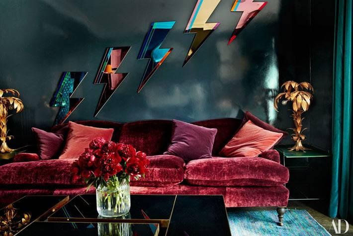 бархатный диван и зеркала в виде молний на стене