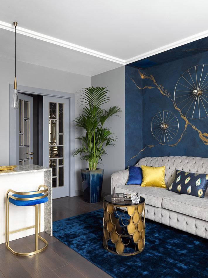 в углу гостиной стоит большая пальма в синем вазоне