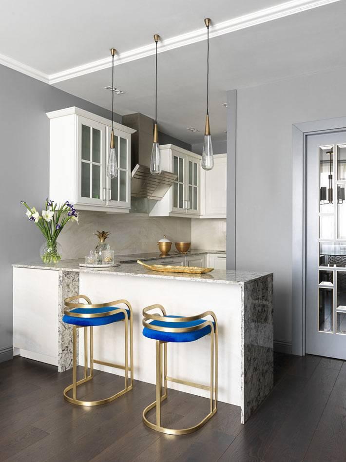 маленькая кухня с барной стойкой и золотыми стульями