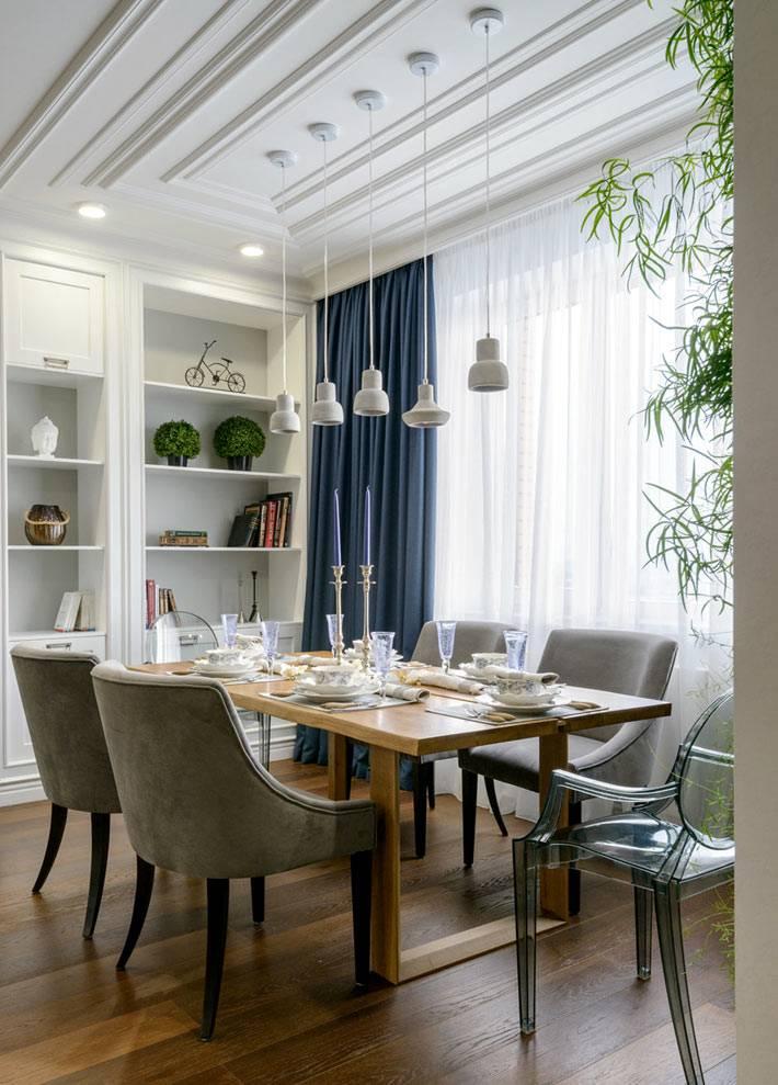 роскошный обеденный стол возле окна и фитостены в квартире