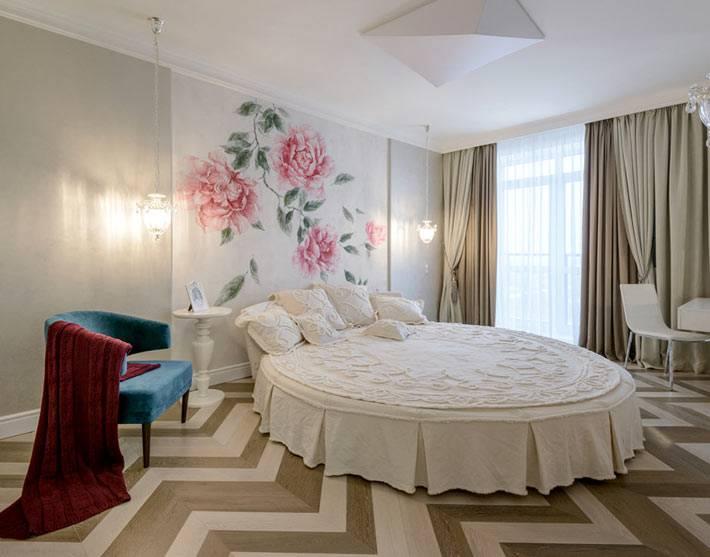 круглая белая кровать в спальне с росписью на стене