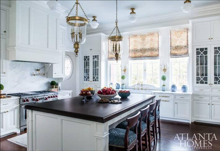 просторная белоснежная кухня с большим островом фото