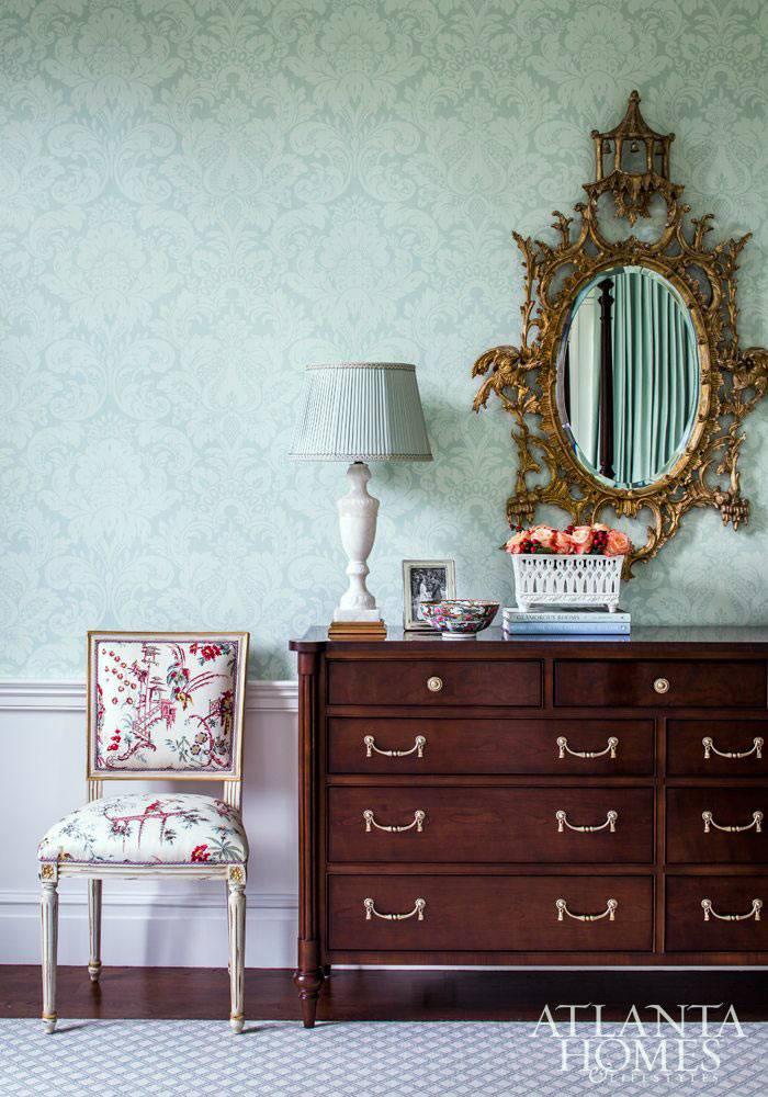 зеркало в резной раме над коричневым комодом в спальне