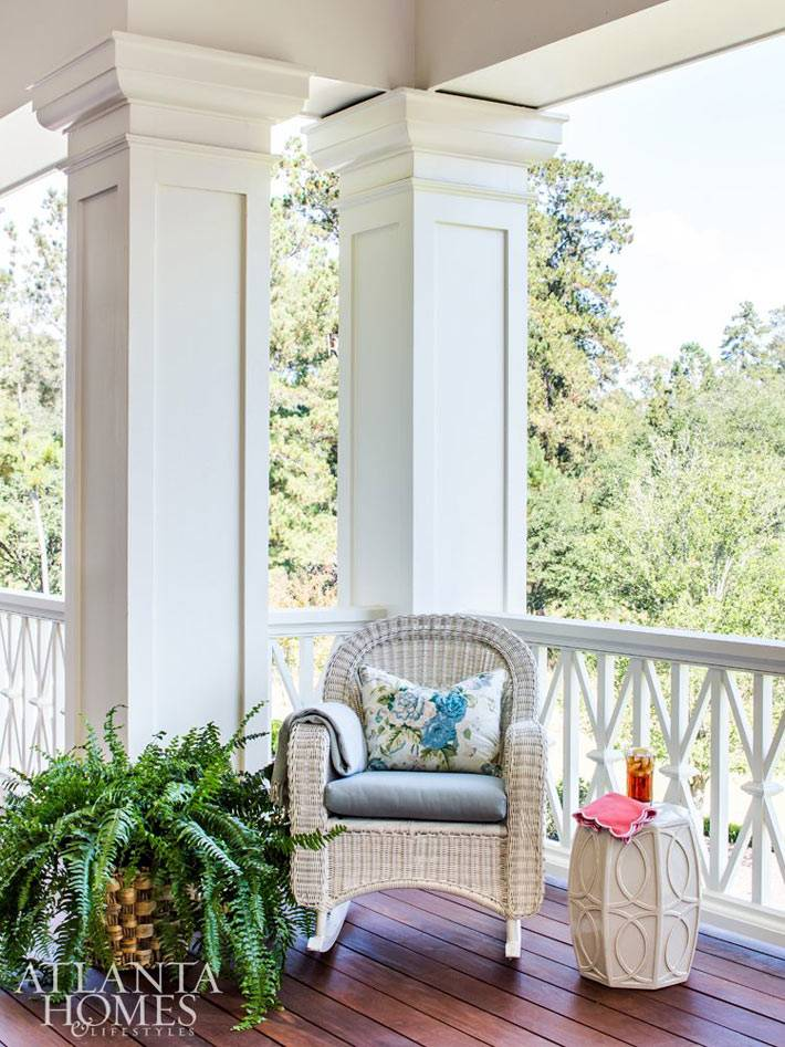 белое плетеное кресло на деревянной веранде дома