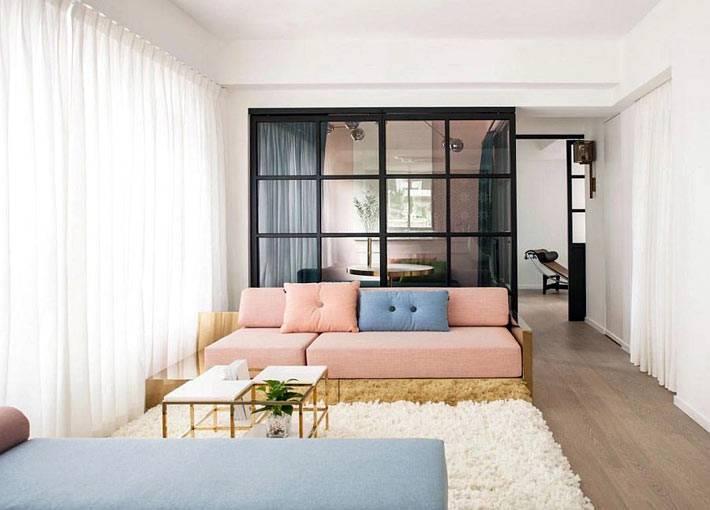 сдержанный дизайн гостиной с розовым диваном