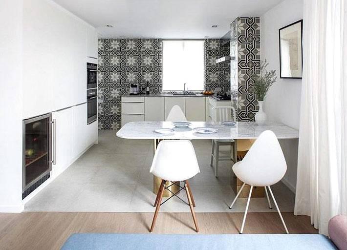 белый интерьер кухни с одной серой стеной,, облицованной плиткой